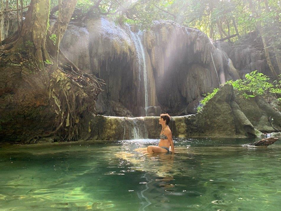 showering under waterfall in Moyo, Indonesia